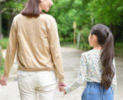 娘と手を繋いで仲良くあるくシングルマザー